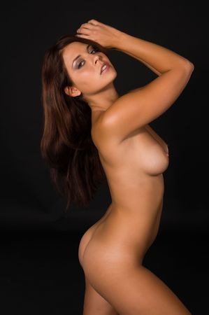 Beautiful young brunette posing nude on a black background