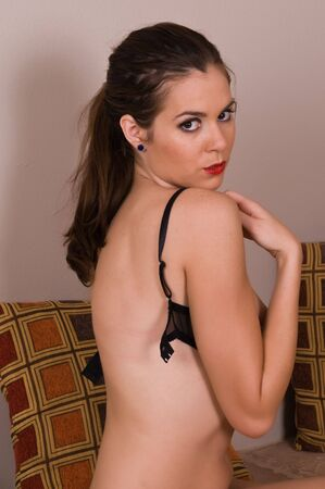 Pretty young brunette taking off her bra Stock Photo - 5799803