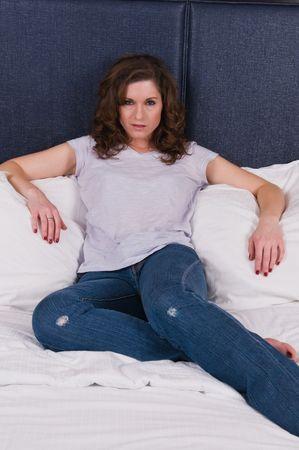 かなりカジュアル服装ブルネットのベッドに座り 写真素材