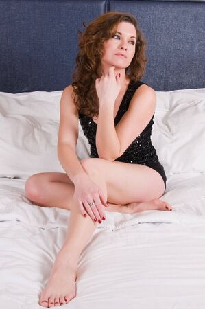 Pretty brunette sitting up in bed photo
