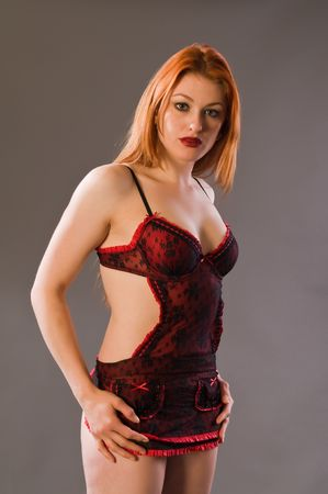 undergarment: Beautiful young redhead in red and black lingerie Stock Photo