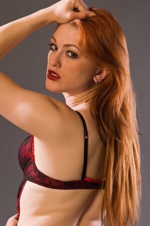 Beautiful young redhead in red and black lingerie photo