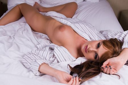 Beautiful brunette wearing a white shirt in bed photo