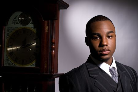 grandfather clock: Dramatic portrait of a dignified young black man in a dark suit Stock Photo
