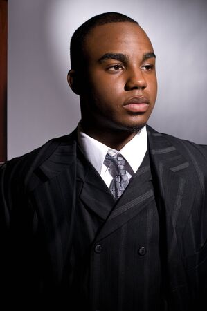 dignified: Dramatic portrait of a dignified young black man in a dark suit Stock Photo
