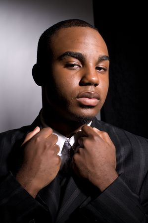 Dramatic portrait of a dignified young black man in a dark suit Stock Photo