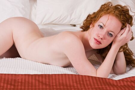 Pretty pale redhead lying nude in bed Stock Photo - 7013916