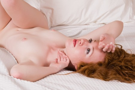 Pretty pale redhead lying nude in bed Stock Photo - 7013906