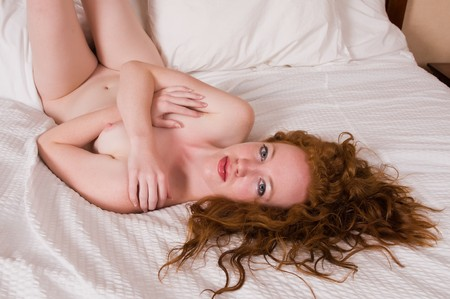 Pretty pale redhead lying nude in bed Stock Photo - 7013933