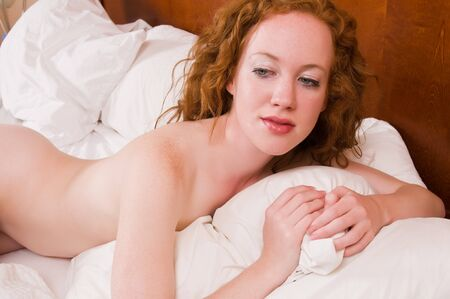 Pretty pale redhead lying nude in bed Stock Photo - 7014081