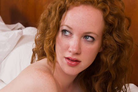 Pretty pale redhead lying nude in bed photo