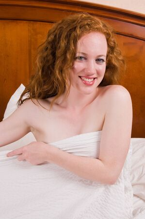 Pretty pale redhead sitting nude in bed photo