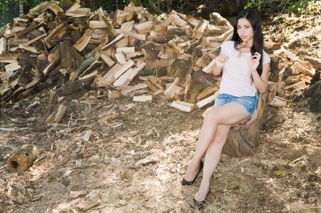 Pretty young Eurasian woman sitting by the woodpile
