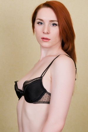 undergarment: Pretty young redhead dressed in black lingerie Stock Photo