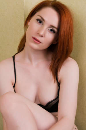 undergarments: Pretty young redhead dressed in black lingerie Stock Photo
