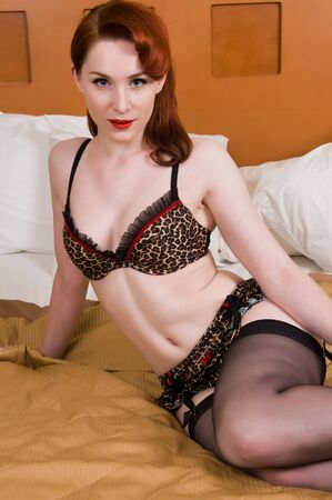 Pretty young redhead dressed in leopard print lingerie photo