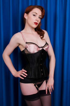 Pretty young redhead dressed in black lingerie photo