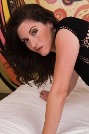 Beautiful brunette in a revealing black knit dress photo
