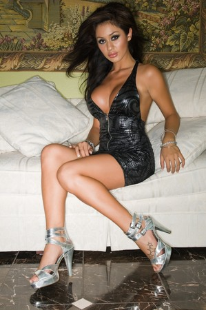 couches: Beautiful young Latina in a shiny gray dress Stock Photo