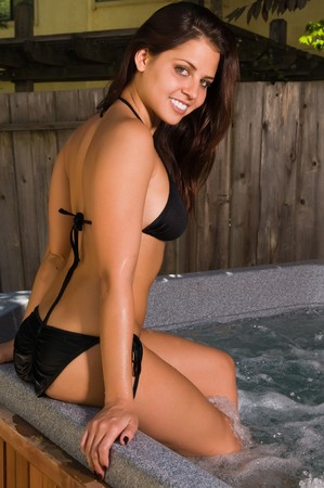 Pretty young brunette in a backyard spa photo