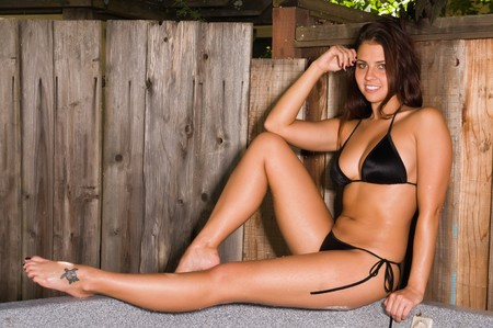 Pretty young brunette in a backyard spa photo