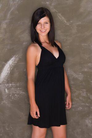 Pretty slender brunette in a black dress photo