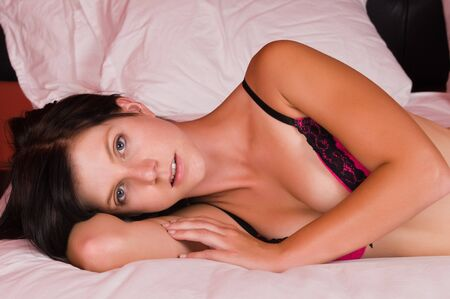 undergarment: Pretty young brunette dressed in pink lingerie Stock Photo