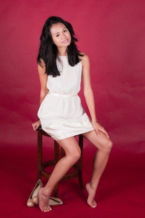 Slender young Singaporean Chinese woman in a white dress photo