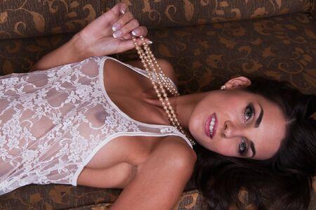 recline: Beautiful young Czech woman lying down in sheer white lingerie