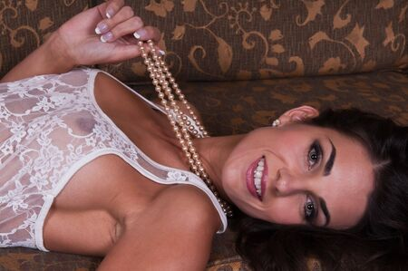 undergarment: Beautiful young Czech woman lying down in sheer white lingerie