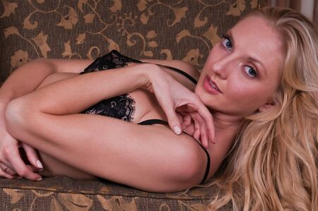 Beautiful tall blonde dressed in black lingerie photo