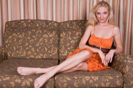 Beautiful tall blonde in an orange dress photo