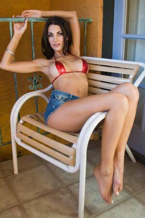 denim shorts: Beautiful Czech woman in a tiny red bikini top
