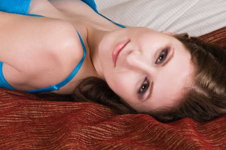 Pretty young brunette dressed in bright blue lingerie photo