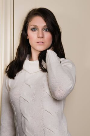 Pretty young brunette in a white knit sweater