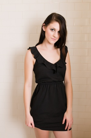 shower stall: Pretty young brunette in a black dress Stock Photo