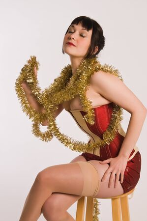 Pretty brunette dressed in a red corset and gold garland Stock Photo - 8476737
