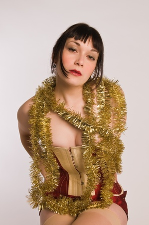 red corset: Pretty brunette dressed in a red corset and gold garland Stock Photo