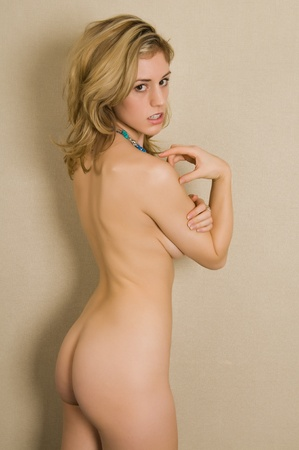 female nudity: Beautiful nude blonde looks back over her shoulder Stock Photo