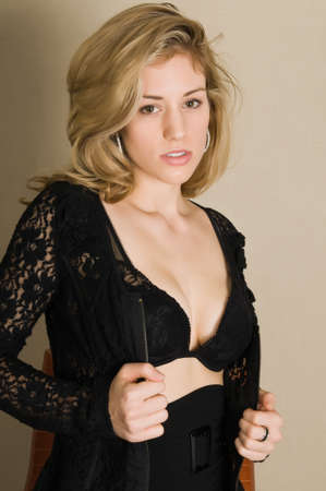 Beautiful young blonde in a black lace dress and bra photo