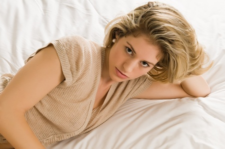 Beautiful young blonde in bed in a tan knit blouse photo