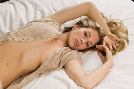 Beautiful young blonde in bed in a tan knit blouse Stock Photo - 8636595