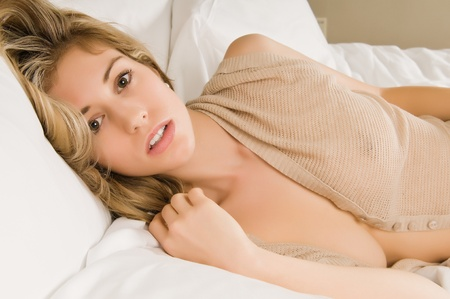 blouse sexy: Beautiful young blonde in a beige knit blouse Stock Photo