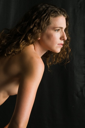 Pretty young nude brunette against black