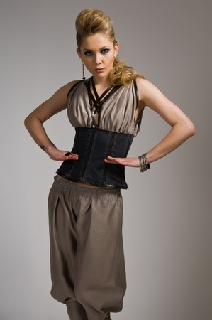 Beautiful tall blonde in a vest and loose pants photo