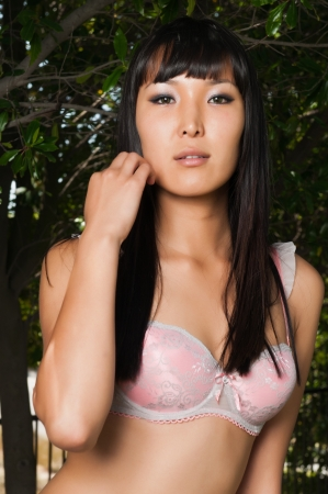 Tall young Mongolian woman outdoors in pink lingerie photo