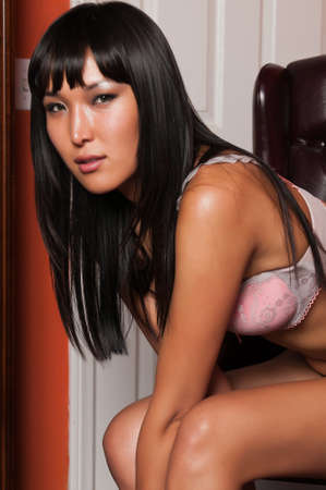 Tall young Mongolian woman in pink lingerie photo