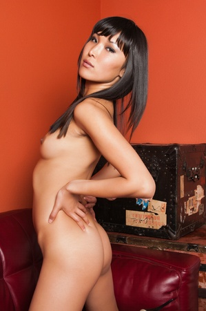 Tall young Mongolian woman sitting nude in a home office Stock Photo - 9711872