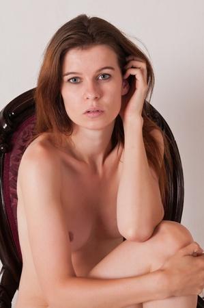 femme se deshabille: Nu de la fille aux cheveux bruns assez dans une chaise antique