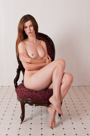 female nudity: Pretty brown haired girl nude in an antique chair Stock Photo